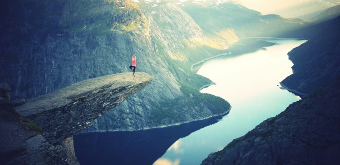 Person does standing yoga pose on a cliff